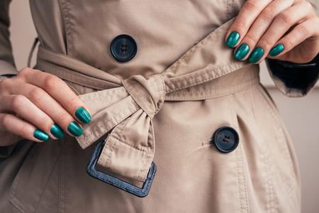 chaqueta: Manos femeninas con un cinturón de lazo manicura brillante en un abrigo, primer plano