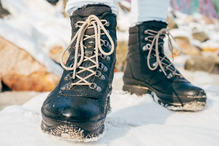 black girl: Female feet in winter boots with laces standing in the snow