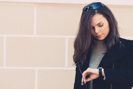 Mooie jonge vrouw in een zwarte jas controleert de tijd op de klok op de achtergrond van beige muur. Warm toning.