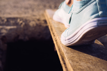 health risk: Female feet in sneakers walking on a narrow board above a large pit. Low-angle shooting, close-up. Stock Photo
