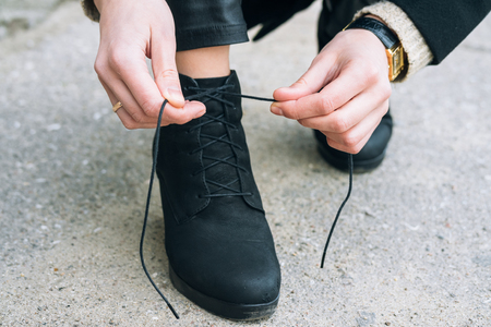 untied: Woman in elegant clothes tying shoelaces on shoes close up. Shoelaces untied during a walk in the city