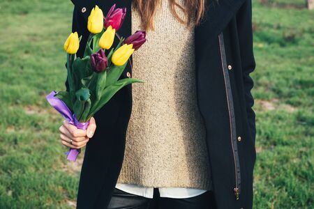 tulips in green grass: Young slim woman in coat standing on green grass and holding a bouquet of tulips in hand Stock Photo