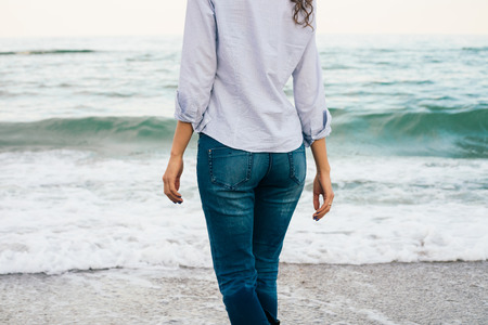 Slank meisje in overhemd en spijkerbroek wandelen langs het strand. Uitzicht vanaf de achterkant Stockfoto