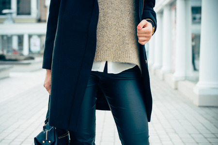 black pants: Details of womens clothing. Close-up of a woman in a sweater, coat, black pants. In her hand female bag.