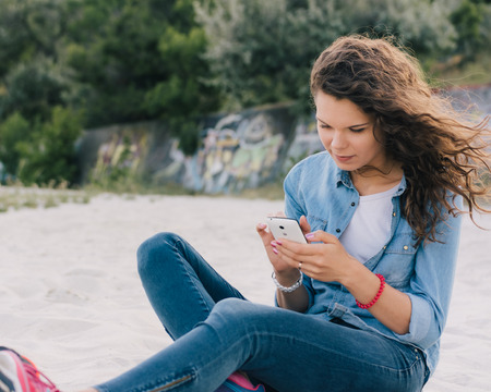 hair wind: Woman in denim clothes sitting on the beach sand and using a mobile phone Stock Photo