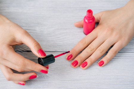 nails: Female hands painted nails with red lacquer Stock Photo