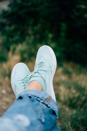 Closeup of female legs in jeans and sneakers on a background of trees. Shallow depth of field, copy space. Standard-Bild
