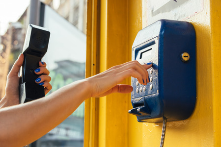 pay phone: Female hands using the pay phone in the city