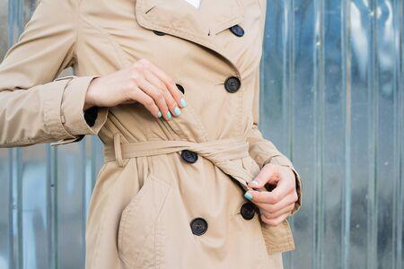 coat and tie: Woman in beige coat tie belt at the waist