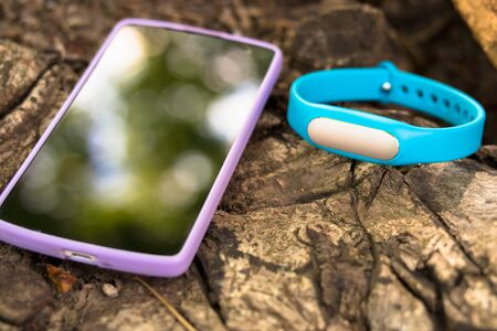 Fitness tracker and smart phone lying on a tree stump in the forest