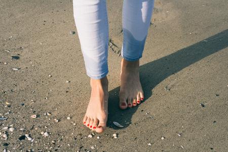 Desnudos pies femeninos caminando en la arena mojada en la playa