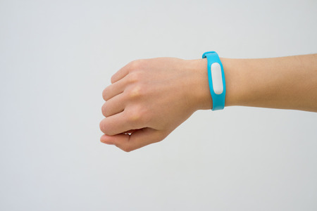 Blue fitness tracker closeup on a female hand. White background, not isolated.