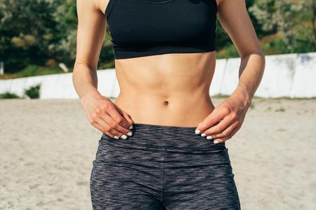 flat stomach: Primer plano de la niña deportivo con un vientre plano en la playa. Ella se da la mano con la manicura blanca en la cintura.