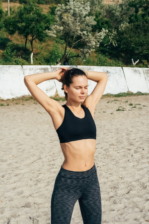 Young slim girl in sportswear doing morning exercises at the beach in summer, vertical framing