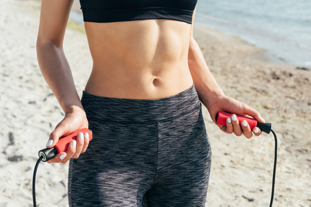 flat stomach: Close-up of a girl with a flat stomach with a skipping rope in her hands on the beach Stock Photo