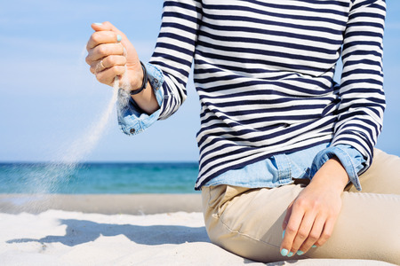 scatters: Close-up of a girl in a striped T-shirt on the beach which scatters sand on the wind