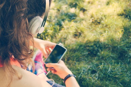 cropped image: Cropped image of a girl in headphones listen to music and use a smart phone on the lawn in the summer, yellow toning