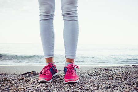 sports shell: Female legs in pink sneakers standing on the beach near the water in the evening