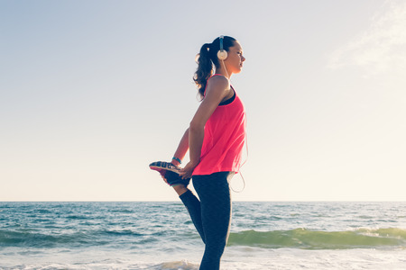 accomplishing: Sport girl on the beach in headphones does sports exercises in the morning