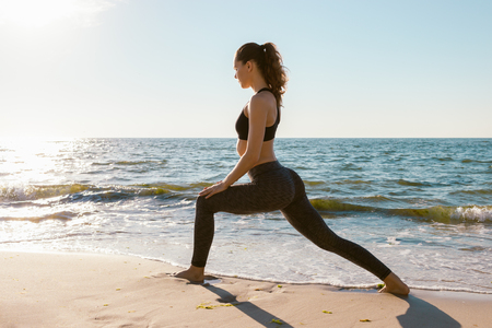 Sport girl on a beach doing lunges exercises. Concept of of a healthy lifestyle. Stock Photo