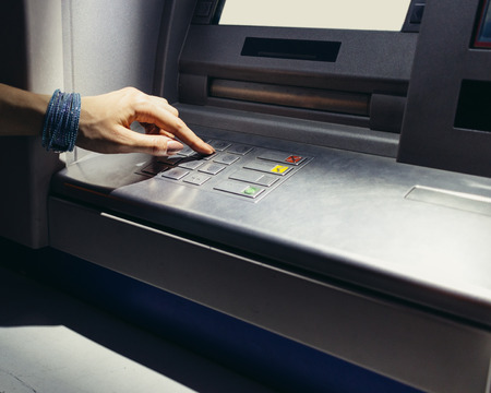secret code: Female hand entering the secret code in the ATM at night on the street