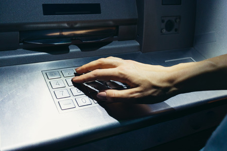 enters: Womans hand enters the secret code at the ATM on the street at night Stock Photo