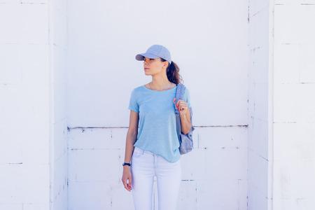 chica delgada que llevaba una gorra, pantalones vaqueros y una camisa azul con una mochila sobre un fondo de paredes blancas