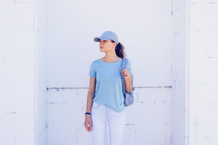 Slender girl wearing a cap, jeans and a blue shirt with a backpack on a background of white walls