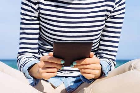 blue stripe: Close-up of a girl in a striped T-shirt with an e-book in hands on the beach Stock Photo