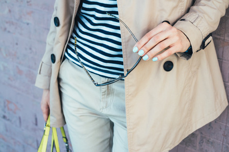 beige: Clothing Details: woman in beige coat holding sun glasses and handbag close-up Stock Photo