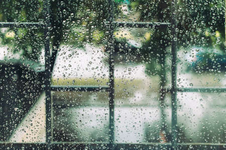 metall and glass: Wet window in drops during the summer rain, vintage toning