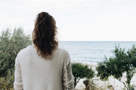 mujer mirando el horizonte: Mujer elegante con el pelo rizado que mira el mar en el otoño