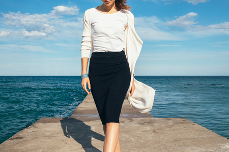 Elegant woman in a skirt and cardigan walks on the background of the sea on a sunny day Stock Photo