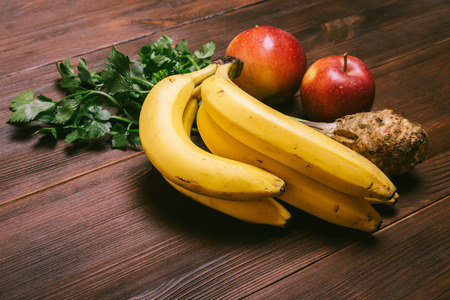 Bunch of bananas, celery root and red apples on a dark wooden table Stock Photo