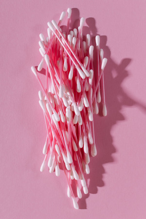 Bunch of cotton swabs on a pink background closeup, vertical framing