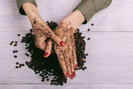 Young woman massaging a hand with coffee scrub, top view