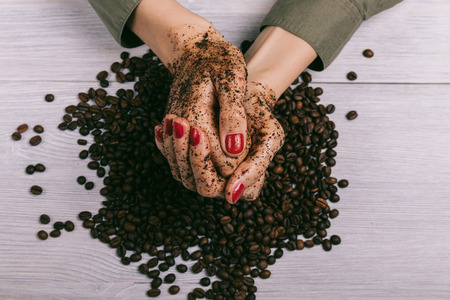Close-up of female hands coated with scrub and coffee beans, top view