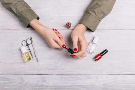 medium body: Woman paints her nails with red lacquer, top view