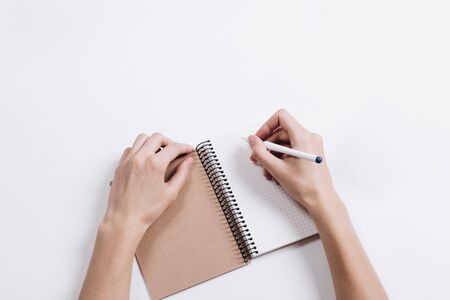 Close-up of female hands writing in Notepad with a pen on a white table
