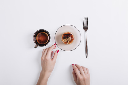Female hand with red manicure takes the cake from the table, top view Standard-Bild