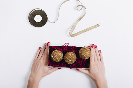 woman's hands: Top view of a womans hands with red nail polish holding a box of Christmas decorations on a light background