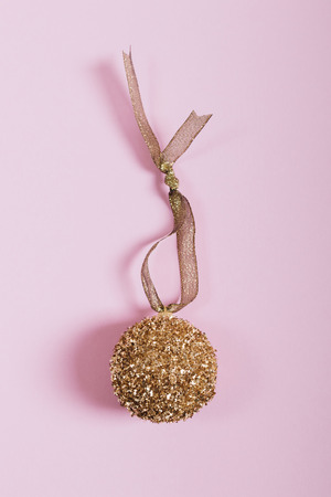 Golden Christmas ball with a ribbon on a pink background, top view, vertical framing