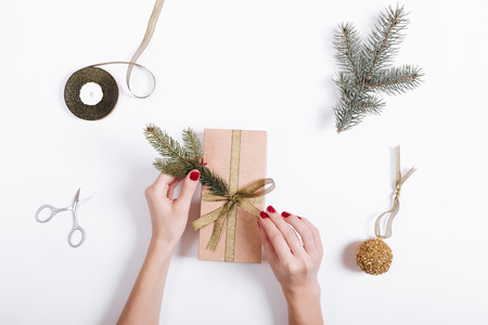 Top view of a female hands pack and decorate the box with gifts on a white background