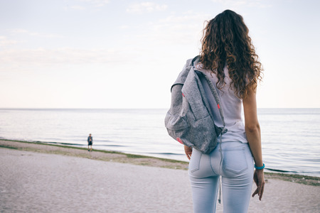 Young sporty woman with curly hair, wearing jeans and a backpack standing on the beach and looking at sea, view from the back