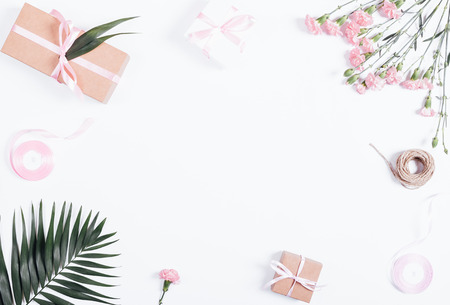Festive composition: boxes with gifts, ribbons and flowers on white table, top view