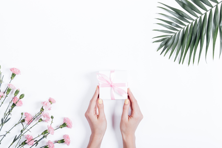 Top view of a female hands holding a small box with a gift and a ribbon on a white background