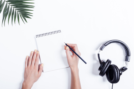 Female hands with a notebook and pencil, headphones and plant on white table, top view