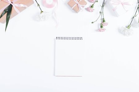 Festive composition: notebook, boxes with gifts, ribbons and flowers lie on a white table top view Stok Fotoğraf