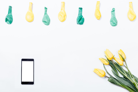 Yellow flowers, mobile phone, and balloons on a white table, top view Stock Photo