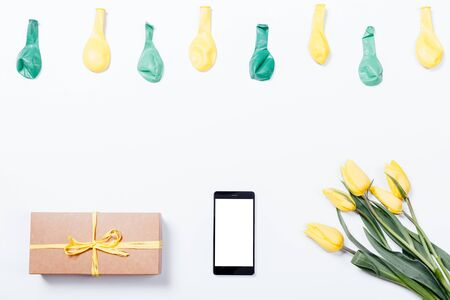 Yellow flowers, mobile phone, gift box with a ribbon and balloons on a white table, top view